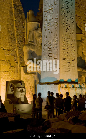 Pylon with seated figures and obelisk of Ramesses II illuminated in the evening, head of Ramesses II at the front, - Stock Photo