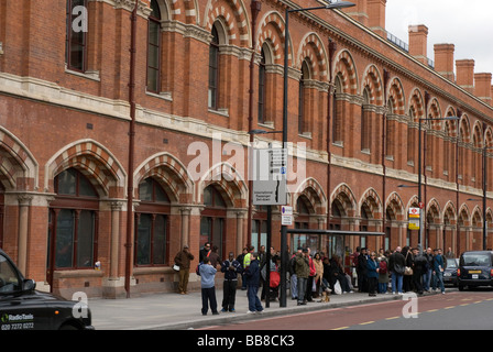 People queuing for a bus outside St Pancras Station, Kings Cross, London UK - Stock Photo