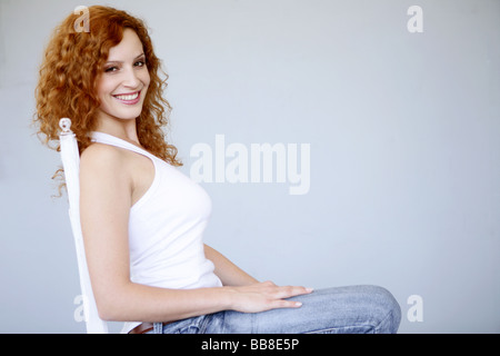 Portrait of young smiling sitting beautiful woman - Stock Photo