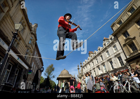 A Street Theatre busker plays a violin while balancing  on a tightrope during Brighton Festival - Stock Photo