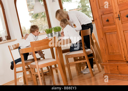 Mother and three children, 1, 3 and 6 years old, at the dining table - Stock Photo