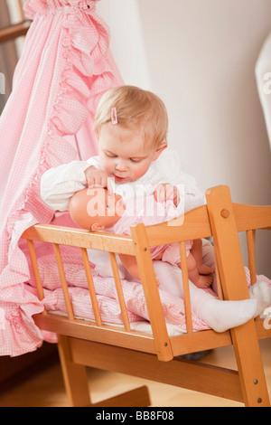 Young girl, 1 year old, sitting in her doll's pram and playing with a doll - Stock Photo