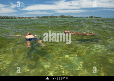 Two Caucasian male tourists relaxing in a clear lake in Bilene, Gaza Province, Mozambique, Africa - Stock Photo