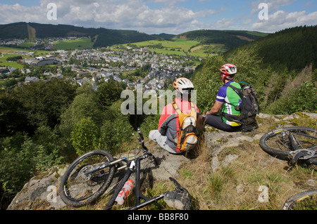 Mountain bike riders resting on Orenberg Mountain with a view over Willingen, Hesse, Germany, Europe - Stock Photo