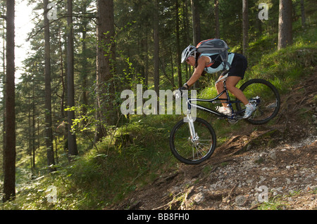 Female mountainbike rider riding along a root trail in a forest near Garmisch, Upper Bavaria, Bavaria, Germany, - Stock Photo