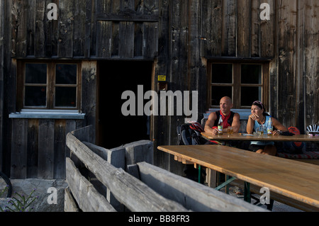 Montainbike riders, female and male, taking a break above the Oberbrunn Alm alpine pasture near Scharnitz, Tyrol, - Stock Photo