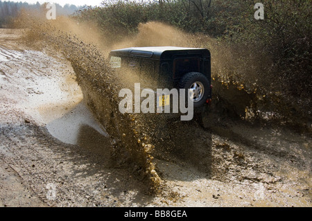 A Landrover Defender driving along a muddy track on an off road exercise - Stock Photo