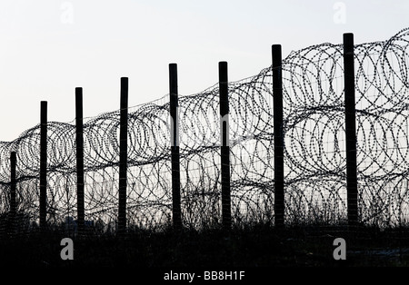 Fence, secured with NATO wire, barbed wire - Stock Photo