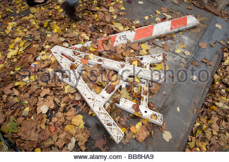 fallen over sawhorse on the sidewalk with autumn leaves - Stock Photo
