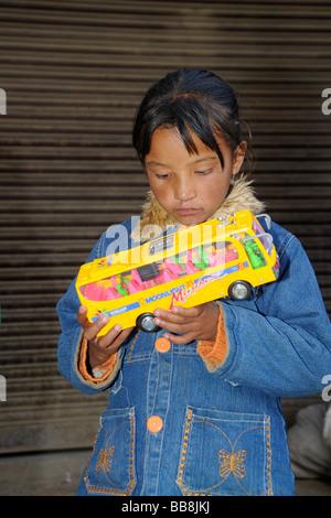 Ladakhi child gazing in wonder at a cheap plastic toy, Leh, Ladakh, North India, Himalayas, Asia - Stock Photo