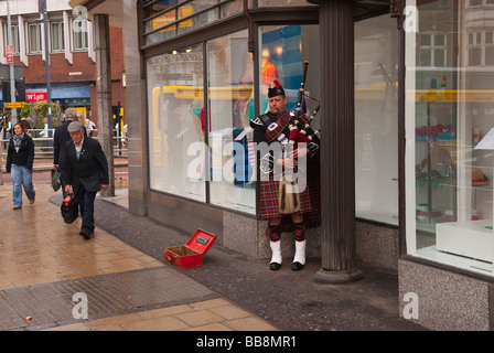 A  scotsman playing the bagpipes and busking in the streets of Norwich,Norfolk,uk - Stock Photo