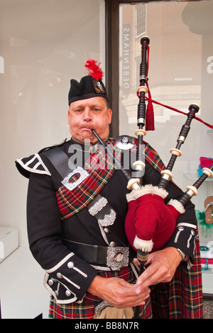 A close up of a scotsman playing the bagpipes in the uk - Stock Photo