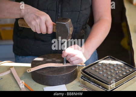 Leather craftsman stamping name in leather wristband, Luxembourg - Stock Photo