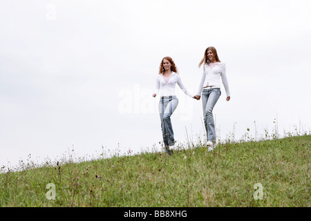 Two teenagers walking on a field - Stock Photo