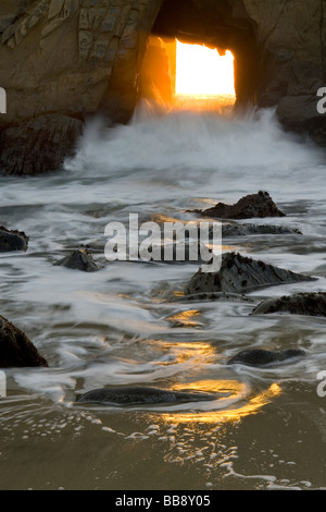 The sun sets through a window to the Pacific - Pfeiffer State Beach, Big Sur Coast, California, USA. - Stock Photo