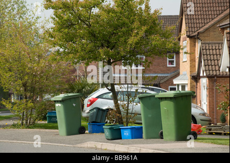 Row of green wheelie bins containing rubbish and plastic recycling bins in a street waiting for collection - Stock Photo