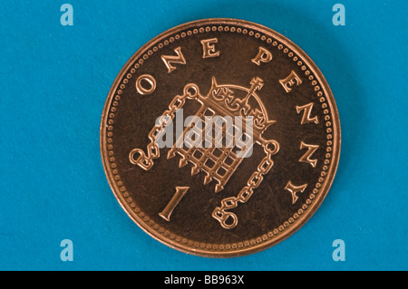 One shiny new one penny coin against a blue background - Stock Photo