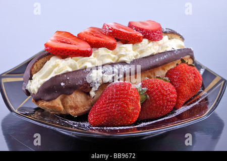 Rich chocolate eclair desert with strawberries on a plate - Stock Photo