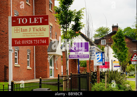 For Sale and 'To Let' signs from various local estate agents outside a newly built block of flats in Frodsham Cheshire - Stock Photo