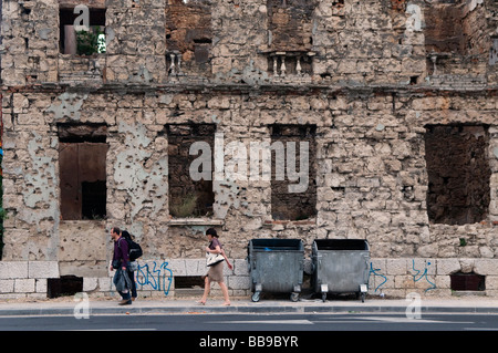 Pedestrians walk past a house showing shrapnel damage from the 1992-95 war in the town of Mostar in Bosnia Herzegovina - Stock Photo