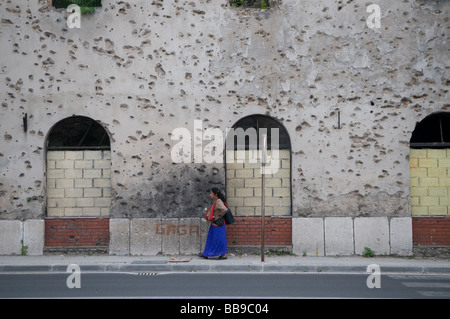 A gypsy woman walk past a house showing shrapnel damage from the 1992-95 war in the town of Mostar in southern Bosnia - Stock Photo