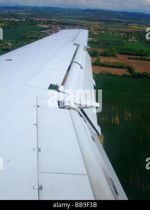 Embraer ERJ-145  aircraft wing with split flaps (model Fowler) down during the final step on landing. - Stock Photo
