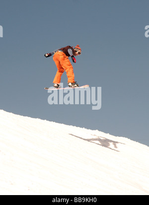 Winter Sports;Snow Boarding;Male about to land after 'Big Air' jump. - Stock Photo