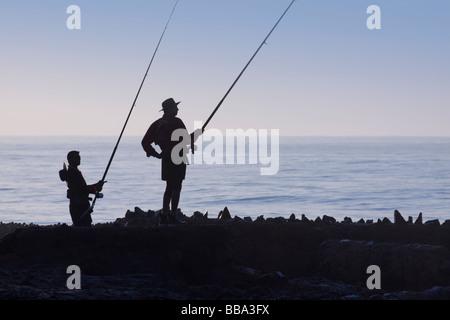 Two fisherman in silhouette at dawn fishing off seaside rocks. Backlit. Silhouette. Durban, KwaZulu Natal, South - Stock Photo