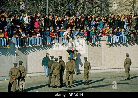 Border soldiers and people on the Berlin Wall at Brandenburg Gate, the day after the fall of the Berlin Wall, Berlin - Stock Photo