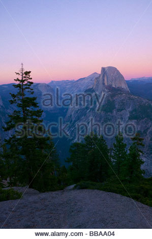 A colorful fall sunset colors the sky over Half Dome and the glacier carved Yosemite Valley. - Stock Photo