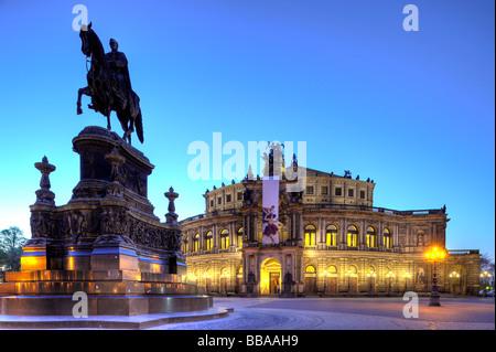Semperoper Opera house with flags and illuminated at night and Koenig Johann memorial, Theaterplatz square, Dresden, - Stock Photo