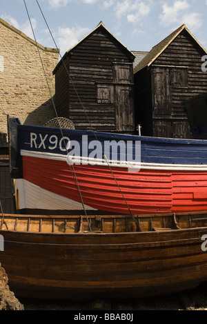 weathered fishermens boat and black huts in Hastings Kent - Stock Photo