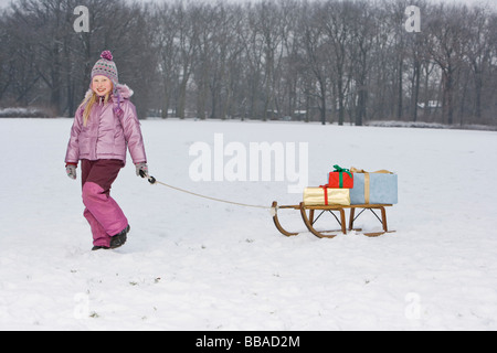 A young girl pulling a sled with presents on it - Stock Photo