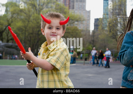A young boy wearing devils horns and holding a pitchfork, Central Park, New York City - Stock Photo