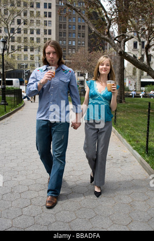A young couple walking through a city park holding hands, Central Park, New York City - Stock Photo
