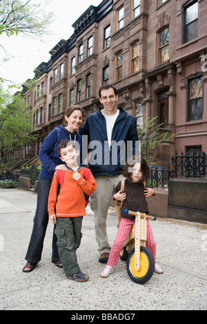 A family standing in front of a row of brownstone townhouses, Brooklyn, New York City - Stock Photo