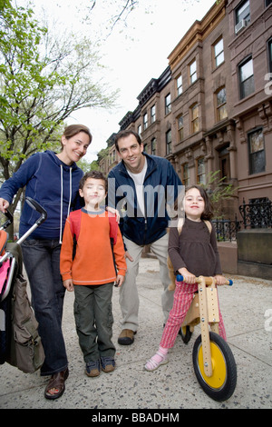 A family standing together on a sidewalk, Brooklyn, New York City - Stock Photo