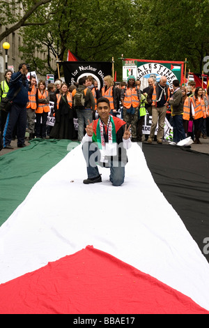 Palestinian protester in London standing on giant flag - Stock Photo
