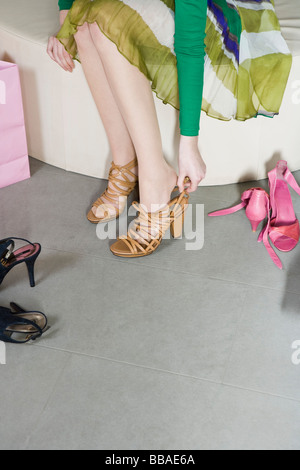 A young woman trying on shoes in a shop - Stock Photo
