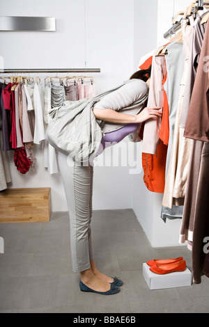 A young woman looking through a clothes rail in a shop - Stock Photo