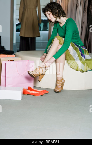 A woman trying on shoes in a store - Stock Photo