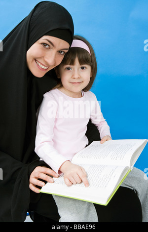A mother wearing a Hijab and her daughter reading a book - Stock Photo