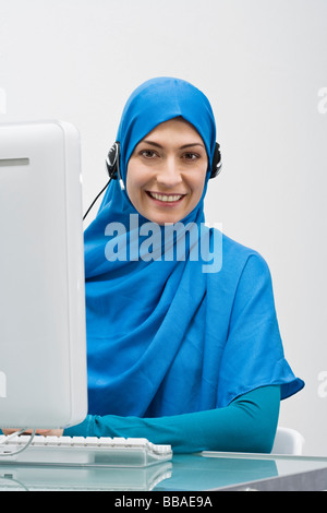 A woman wearing a Hijab and working in a call center - Stock Photo