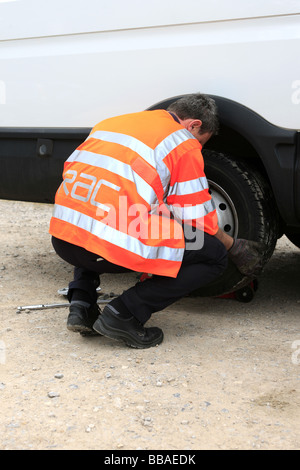 Breakdown recovery man changes the tyre on a white panel van - Stock Photo