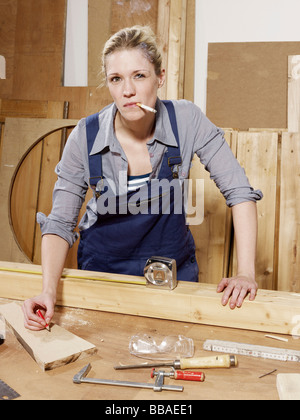 A woman smoking while working in a wood workshop - Stock Photo