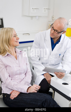 A dentist and a patient in a dental examination room - Stock Photo