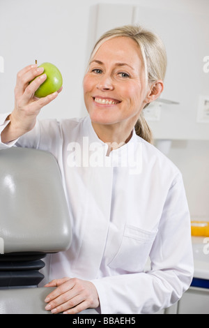 Portrait of a dental assistant holding an apple - Stock Photo