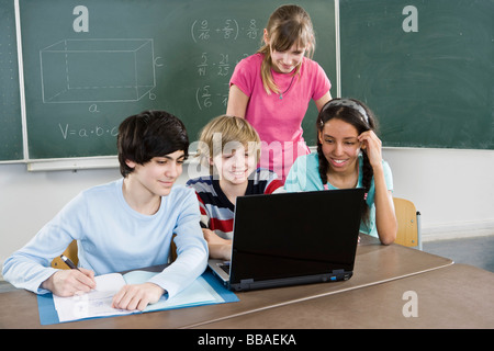 School students using a laptop - Stock Photo