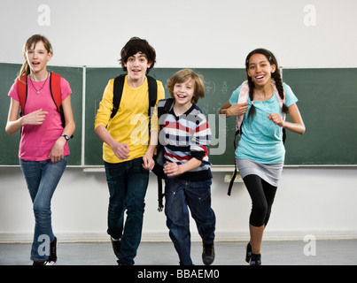 School students running together in a classroom - Stock Photo
