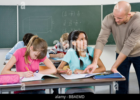 A teacher working with students in a classroom - Stock Photo